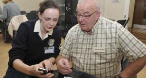 Tom McInernery is shown how the functions on his mobile phone work by Patricia Hinterleitner from the Dominican College, Wicklow.