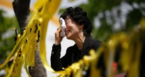 A mourner cries next to yellow ribbons dedicated to missing and dead passengers of sunken passenger ship Sewol, after paying tribute at the official memorial altar in Ansan today. Photograph: Reuters/Kim Hong-Ji