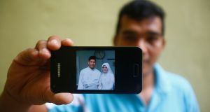 Mohamad Sharil Shaari (36), nephew of Razahan Zamani, a passenger on the missing Malaysian Flight MH370, shows a wedding picture that he took of Razahan and Razahan's wife Norli Akmar Hamid, on his mobile phone during an interview near his house in Taman Sri Sentosa in Kuala Lumpur on May 2nd 2014. Photograph: Samsul Said/Reuters
