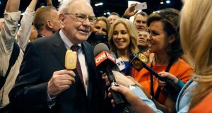 Berkshire Hathaway chief executive Warren Buffett talks to reporters while holding an ice cream at a trade show during the company's annual meeting in Omaha, Nebraska. The conglomerate said quarterly profit declined 4 per cent, falling short of analysts' forecasts. Photograph: Rick Wilking/Reuters