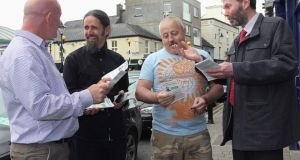 Independent candidate Luke Ming Flanagan gets a little help from his friend, whistelblower John Wilson, as he canvasses Eamon Murray and Sean Roche in Cavan town. Photo: Lorraine Teevan