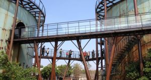 Visitors traverse elevated walkways between former liquid sugar storage tanks at the old sugar factory in Tainan city that is now home to the Ten Drum group. Photograph: Peter Murtagh