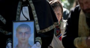 A funeral steward holds a picture of 17-year-old Vadim Papura during a religious service  in Odessa yesterday. Photograph: AP Photo/Vadim Ghirda