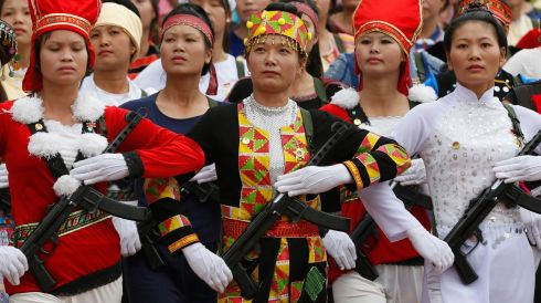 Female militants in the attire of ethnic minorities, on the march.  Photograph: Kham/Reuters