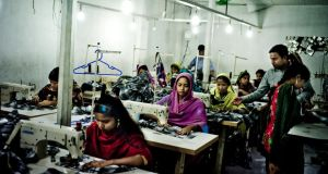 Workers sew clothes at an unregulated factory in Dhaka, Bangladesh. Photograph: Tomas Munita/The New York Times