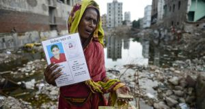 A mother shows a photograph of her daughter, who died in the Rana Plaza collapse. Photograph:  MUNIR UZ ZAMAN/AFP/Getty Images)