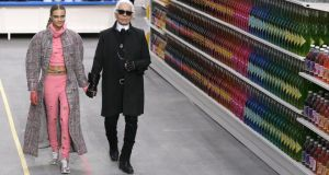 Consumer culture: Karl Lagerfeld with model Cara Delevingne at this season's Chanel Shopping Centre fashion show, in Paris. Photograph: Patrick Kovarik/AFP/Getty Images