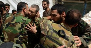 Newly-released forces loyal to Syria's President Bashar al-Assad are greeted by their comrades after their release by rebels in Aleppo's Bustan al-Qasr. Photograph: Reuters