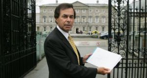 Alan Shatter with a copy of a HSE report on childcare outside Leinster House in 2010. Photograph: Cyril Byrne/The Irish Times