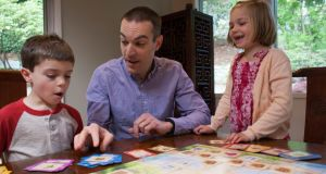 Dan Shapiro (centre) plays Robot Turtles – which Shapiro designed to teach basic computer programming skills – with his children at his home in Mercer Island, Washington. Photograph: David Ryder/The New York Times