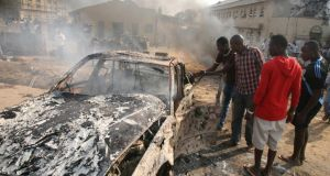 Men look at the wreckage of a car following a bomb blast outside the Nigerian capital Abuja in December, 2011. Photograph: AFP/Getty Images
