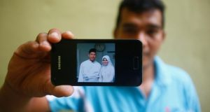 Mohamad Sharil Shaari (36) nephew of Razahan Zamani, a passenger on the missing Malaysian Flight MH370, shows a wedding picture that he took of Razahan and Razahan's wife Norli Akmar Hamid, on his mobile phone during an interin Kuala Lumpur. Photograph: Reuters