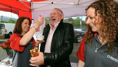 Open wide!  Mary Cahilltry and Eileen O'Meara tempt Michael O'Mahony with some roasted locusts. Photograph: Don MacMonagle