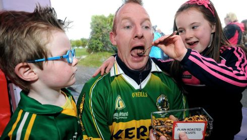 Don't be a wuss daddy! Former Kerry footballer Liam Hassett and his children Mark and Sophie faces down locusts.  Photograph: Don MacMonagle