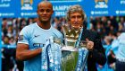 Manchester City's captain Vincent Kompany and manager Manuel Pellegrini pose  with the English Premier League trophy. Photograph:   Darren Staples/Reuters