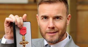 Gary Barlow holding his OBE. The Take That star faces calls to hand back his OBE over claims he invested in a tax avoidance scheme. Photograph: PA Wire