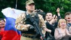 A bodyguard hold his weapon during a rally to mark and celebrate the announcement of the results of the referendum on the status of Luhansk region in Luhansk today. Photograph: Valentyn Ogirenko /Reuters