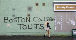 A woman walks past graffiti, a reference to a project by Boston College, on a wall off the Falls Road, Belfast. Photograph: Paul Hackett/Reuters