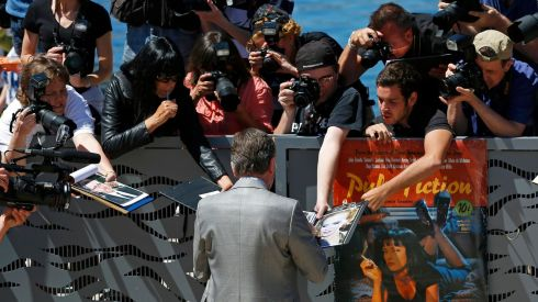 Actor Tim Roth signs autographs as he arrives to attend a photocall for the film Grace of Monaco (Grace de Monaco) out of competition before the opening of the 67th Cannes Film Festival. The Pulp Fiction poster from 20 years ago is there to be signed as well.  Photograph: Yves Herman/Reuters