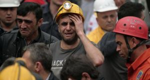 A miner cries as rescue workers carry the dead body of a miner from the mine in Soma, western Turkey, yesterday. Photograph: Emrah Gurel/AP