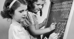 Girls practice their cursive handwriting on a blackboard in 1935. Photograph; Harold M Lambert / Getty Images
