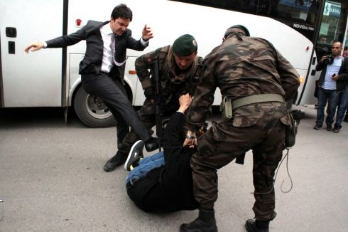 Yusuf Yerkel, a prime ministerial aide (left),  appearing to kick a person who is being wrestled to the ground by two police officers during protests over the fatal mine blast near Soma, Turkey. Mr  Yerkel confirmed to the BBC's Turkish Service that he is the individual pictured in the photograph. Photograph: Depo Photos/EPA