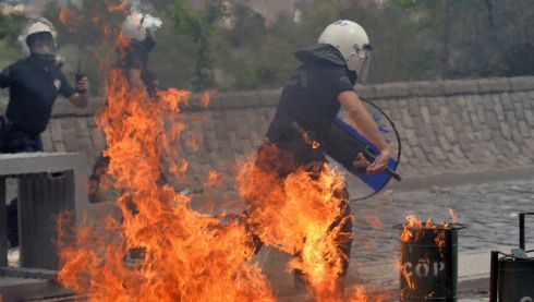 Riot police run away from an exploding fire bomb thrown by protesters as they demonstrate in Ankara, Turkey, over the mass death of miners after a coal mine explosion in Soma. Photograph: Reuters
