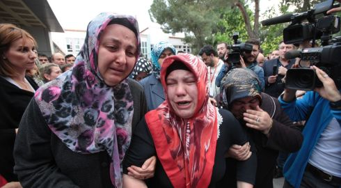Relatives of trapped miners react near the mine as rescue efforts continue.  Photograph: Ahmet Sik/Getty Images