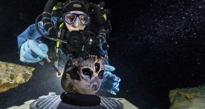 Diver Susan Bird working at the bottom of Hoyo Negro, a large dome-shaped underwater cave on Mexico's Yucatán Peninsula. She carefully brushes the human skull found at the site while her team members take detailed photographs. Photograph: Paul Nicklen/National Geographic