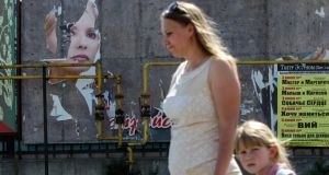 A woman and her daughter walk past a torn poster of Ukrainian politician and presidential candidate Yulia Tymoshenko in Luhansk, eastern Ukraine, yesterday. Photograph: Reuters/Valentyn Ogirenko