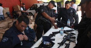 Former vigilantes receive weapons during a swearing in ceremony as members of the Fuerza Rural (Rural Police Force) in Tepacaltepec, Michoacán state. Photograph: Alan Ortega/Reuters