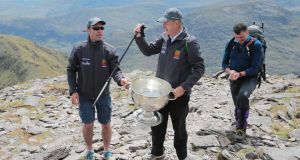 "GAA Commentator Mícheál Ó Muircheartaigh lifts the Sam Maguire Cup on the summit of Carrauntoohil with programme director and former Galway star Alan Kerins (left) and Tom Prendergast, 1969 Kerry All-Ireland winner, during the ""Sam to Summit"" in aid of the Alan Kerins Project. Photograph: Valerie O'Sullivan/Sportsfile."