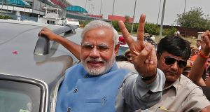 India's next prime minister Narendra Modi, gestures towards supporters from his car upon his arrival at the airport in New Delhi today. Photograph: Reuters