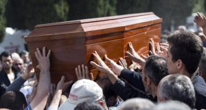 Friends and relatives reach out ot touch the coffin of a miner recovered from the Soma mine in Turkey today. Photograph: Oli Scarff/Getty Images.