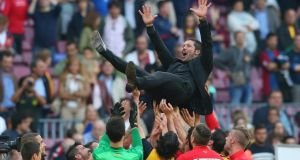 Atletico Madrid coach  Diego Simeone  is thrown in the air by his players after winning the La Liga title after their 1-1 draw against Barcelona  at the Nou Camp. Photograph:  Alex Livesey/Getty Images