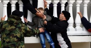 Serbian  soldiers rescue  a boy from a flooded house in the town of Obrenovac, southwest of Belgrade. Photograph: Marko Djurica/Reuters