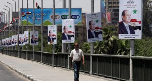 A  man passes under electoral billboards featuring Egyptian presidential candidate and former defense minister Abdel Fattah al-Sissi in Cairo today. Some 163 members of the Muslim Brotherhood were jailed today just over a week before the country's presidential election. Photograph: Khaled Elfiqi/ EPA.