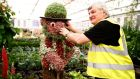A stall holder attaches an eye to a figure on his display of edible leaves such as cabbages and lettuce at the Chelsea Flower Show in London today. Photograph: Reuters