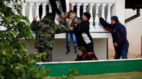 Serbian army soldiers evacuate a boy from a flooded house in the town of Obrenovac, southwest of Belgrade. Photograph: Marko Djurica/Reuters