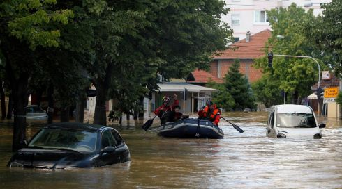 Firefighters evacuate people on a boat in the flooded town of Obrenovac, Serbia. Soldiers, police and villagers battled to protect power plants in Serbia from rising flood waters on Sunday.  Photograph: Antonio Bronic/Reuters