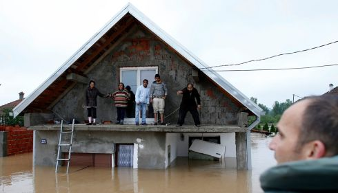 People stand on the terrace of their flooded home as they wait to be evacuated in the town of Obrenovac. Photograph: Marko Djurica/Reuters