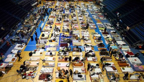Evacuees from the Serbian town of Obrenovac are seen lying on beds in a shelter hall in Belgrade. Two Russian cargo planes carrying food, generators and rescue boats landed in Serbia as part of a relief effort after the worst floods in over a century.  Photograph: Marko Djurica/Reuters