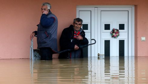 Two men stand in the waters in front of their flooded house as they wait to be evacuated in the town of Obrenovac. Photograph: Marko Djurica/Reuters