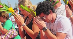 Caroline Wozniacki and Rory McIlroy pray during their visit to a temple in Thailand's beach resort city of Hua Hin in December, 2011. Photograph: Bec Tero/Reuters.