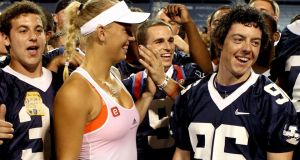 Rory McIlroy and  Caroline Wozniacki  members of the Yale football team after her win over Francesca Shiavone of Italy during the semifinals of the New Haven Tennis Open at Yale on August 26th, 2011 in New Haven, Connecticut. Photograph:  Matthew Stockman/Getty Images