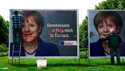 Workers in Berlin paste over vandalised election posters of German Chancellor and head of the Christian Democratic Union (CDU), Angela Merkel, for the  European Parliament vote. Photograph: Thomas Peter/Reuters