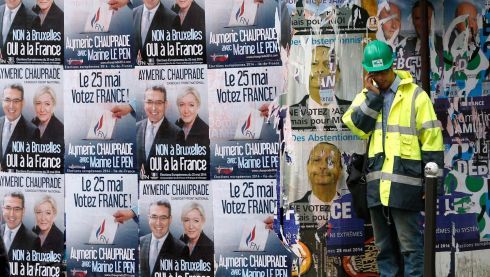 A worker makes a call in front of election campaign posters of Marine Le Pen, France's National Front leader, in Paris. Photograph: Charles Platiau/Reuters