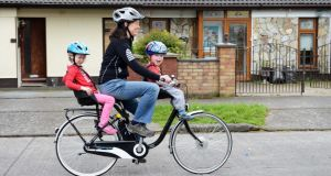 Cliona Brophy on her e-bike with her children Bobby (3) and Alice (5), in Clondalkin, Dublin. Photograph: Eric Luke