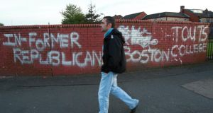 A man walks past graffiti relating to the Boston College tapes on the Falls Road, west Belfast. The PSNI has announced it will seek access to all  remaining recordings which have not already been handed over to them. Photograph: Paul McErlane/EPA