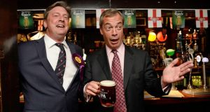 The leader of Britain's United Kingdom Independence Party (UKIP), Nigel Farage (R), holds a pint as he stands with a supporter at the Hoy and Helmet pub in South Benfleet, southern England. Britain's anti-EU party UKIP made strong gains in local elections in England, siphoning support from Prime Minister David Cameron's Conservatives as it capitalized on discontent about immigration and mainstream politics. Photograph: Suzanne Plunkett/Reuters